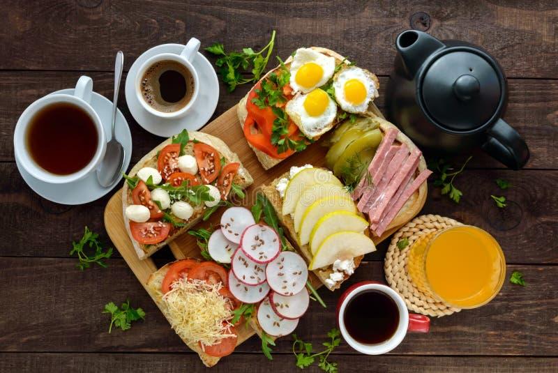 Många sorter av smörgåsar, bruschettaen och te, kaffe, ny fruktsaft - för en familjfrukost royaltyfri bild