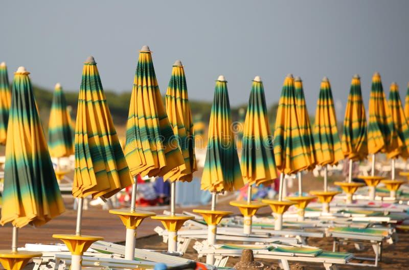 Många stängda paraplyer på havet sätter på land väntande på semesterfirare fotografering för bildbyråer