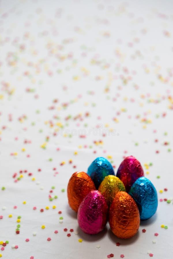 M?nga st?ende kul?ra chokladeaster ?gg p? vit bakgrund och f?rgrika konfettier arkivfoton