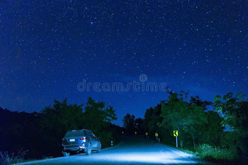Många stjärna på natthimlen med bilen på vägen royaltyfri foto