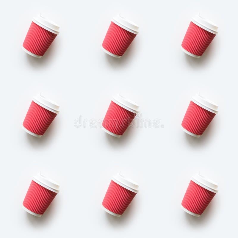Många takeaway pappers- koppar för rött kaffe som sömlös modell på vit bakgrund Lekmanna- l?genhet Top besk?dar arkivfoto