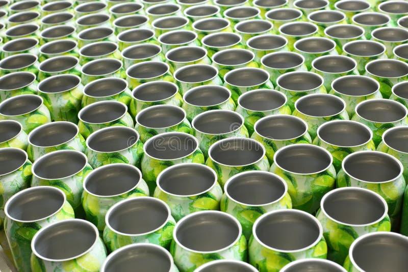 Många tomma aluminiumburkar för drinkar flyttar sig på transportör royaltyfria foton