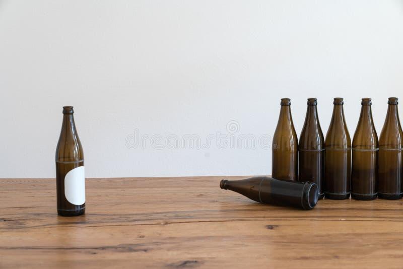 Många tomma bruna ölflaskor på en trätabell royaltyfria foton