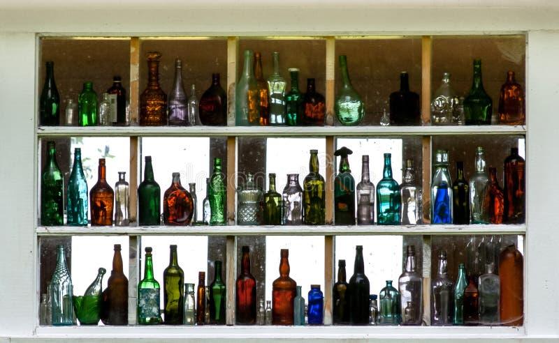 Många tomma färgrika glasflaskor som visas inom ett fönster arkivfoto