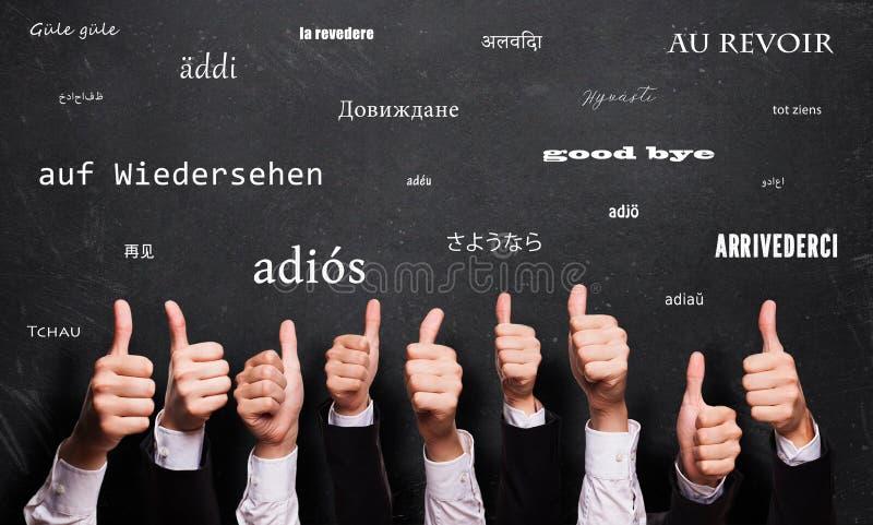 Många tummar upp med ett farväl i många språk framme av en svart tavla arkivbild