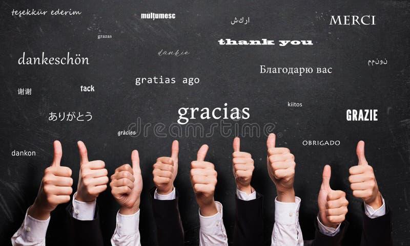 Många tummar upp med ord`en tackar dig ` i många språk framme av en svart tavla royaltyfri foto