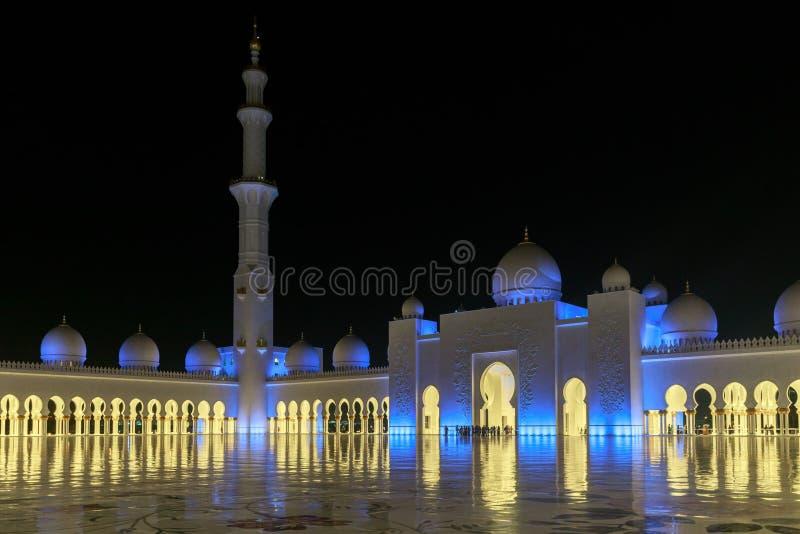 Många turister beundrar de härliga sikterna av Sheikh Zayed Grand Mosque, exponerade med blått ljus i aftonen royaltyfri bild