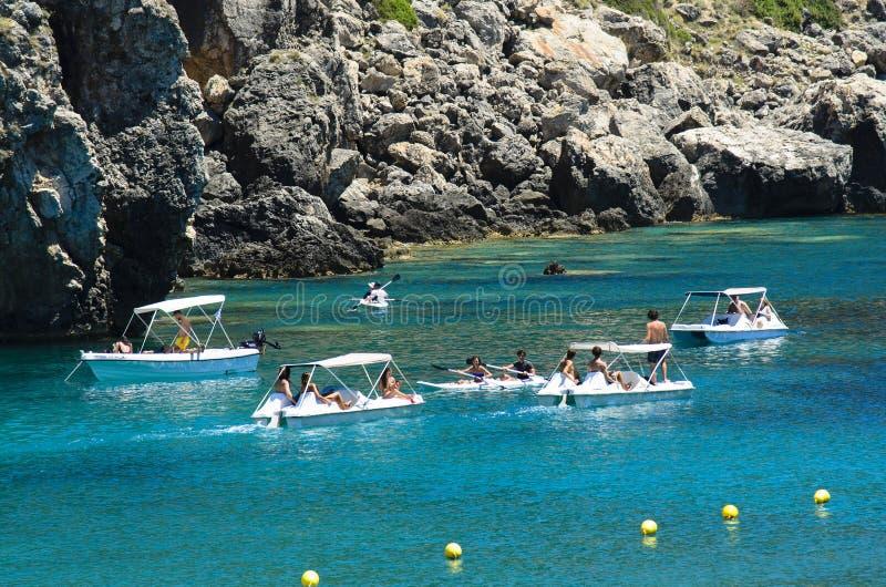 Många turister i en fjärd seglar på paddleboatskanoter, och motorbåtar, havet är turkosgräsplan, på arkivfoton