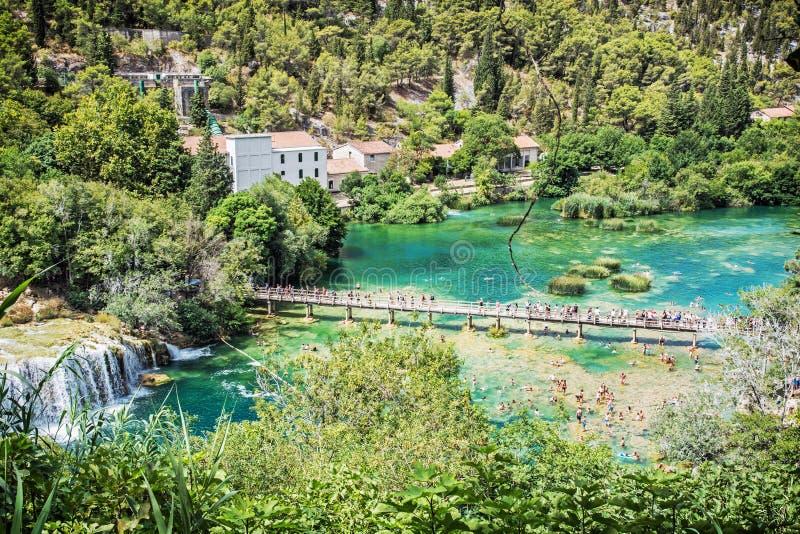 Många turister simmar i floden nära vattenfallen, Krk royaltyfri bild
