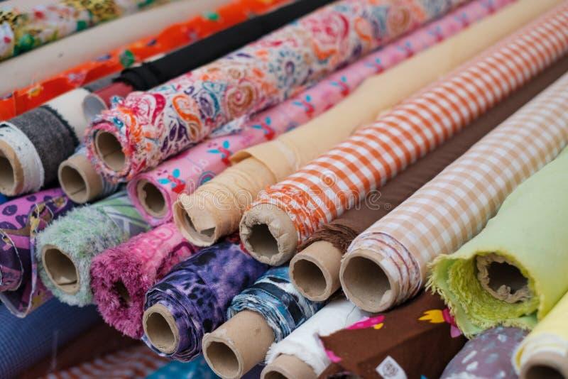Många tygrullar och färgrika textiler på marknaden royaltyfri foto
