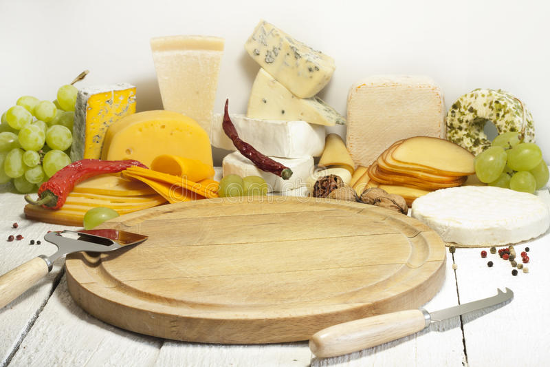 Många typer av ost på skärbrädaabstrakt begrepp royaltyfri foto