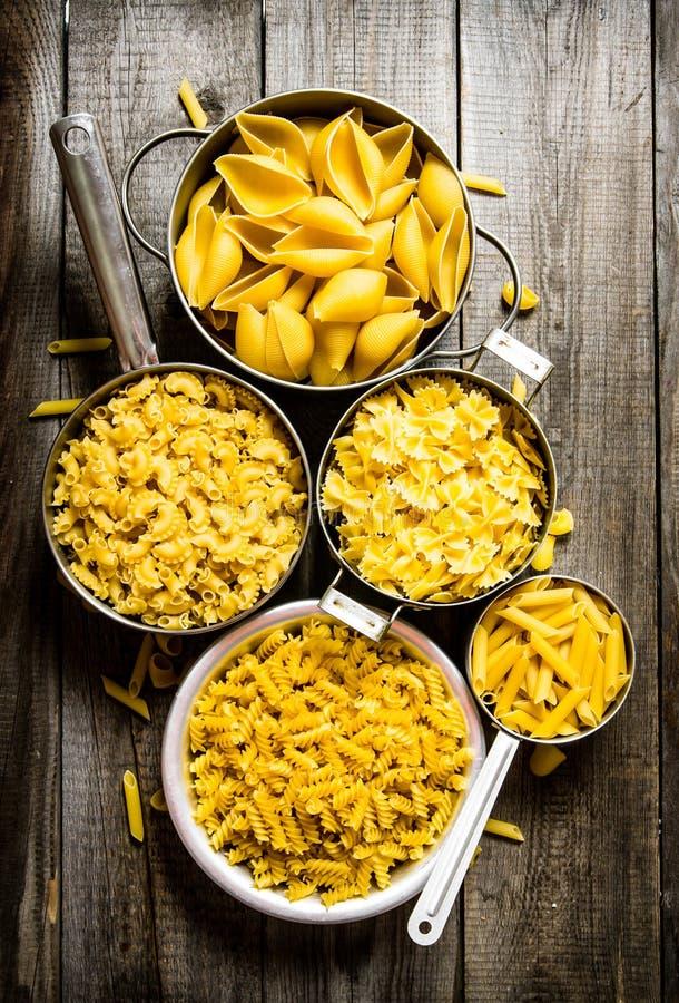 Många typer av torr pasta i krukan arkivfoton