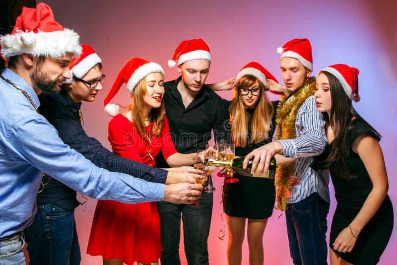 Många unga kvinnor och män som dricker på julpartiet arkivbilder