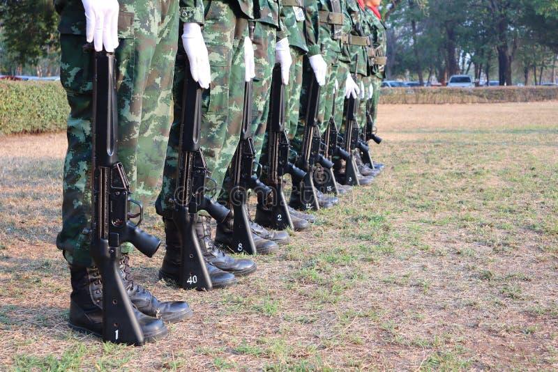 Många unga soldater står med vapen med styrka Ordna till för att slåss naturlig bakgrund arkivbilder
