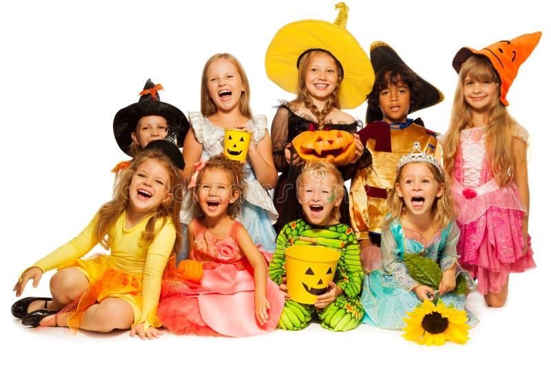 Många ungar sitter i bärande allhelgonaaftondräkter för grupp fotografering för bildbyråer