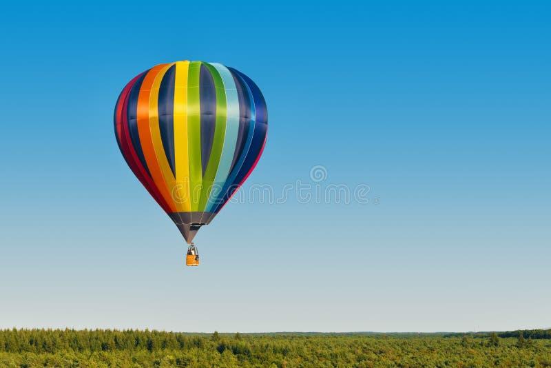 mångfärgad ballong för varm luft som flyger över en skog arkivfoto