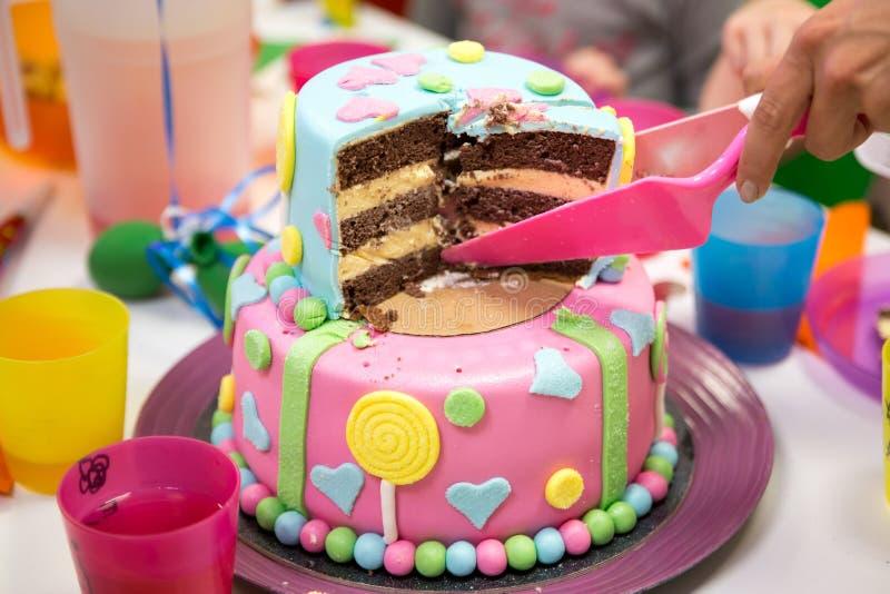 Mångfärgad chokladkaka för födelsedag med godisar i dekorsnitt på tabellen royaltyfri fotografi
