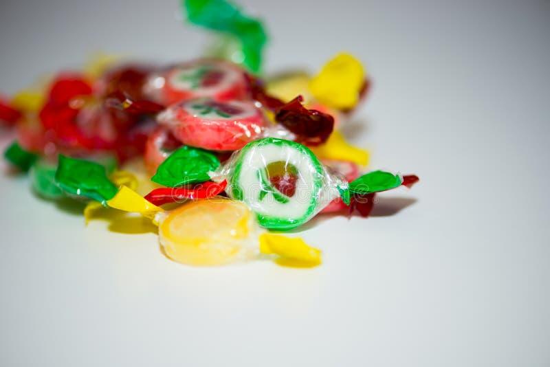 Mångfärgad godis och klubbor på en vit bakgrund royaltyfri bild