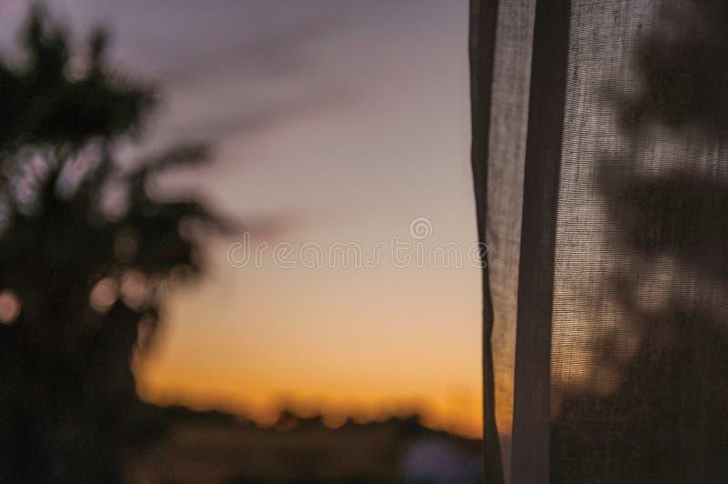 Mångfärgad himmel på solnedgången och en gardin i en lantgård fotografering för bildbyråer