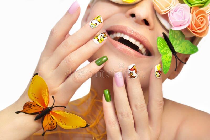 Mångfärgad manikyr med bilder av fjärilar royaltyfria bilder