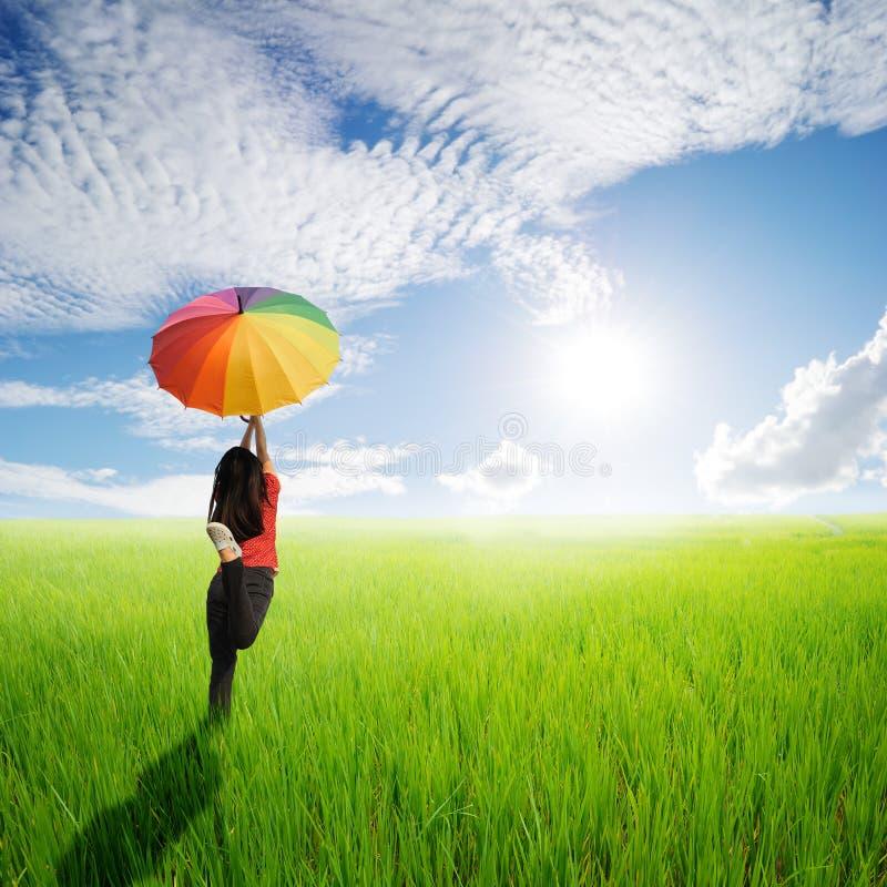 Mångfärgad paraplykvinnabanhoppning i grön risfält- och solhimmel arkivfoto