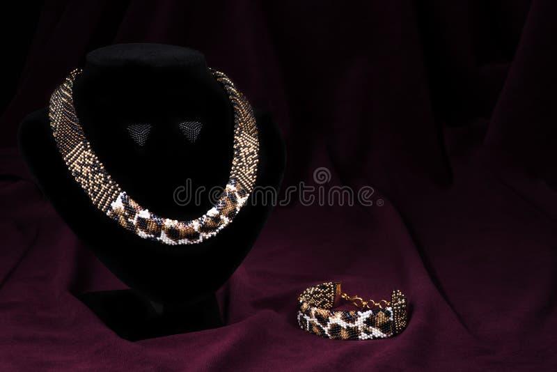 Mångfärgad prydd med pärlor halsband på en skyltdocka, på en svart bakgrund Ställe för inskriften royaltyfri fotografi