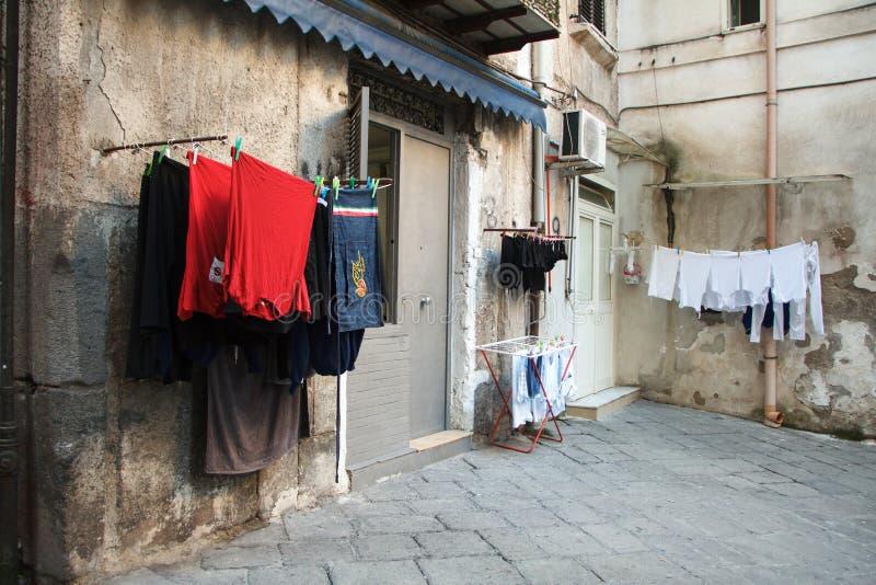 Mångfärgad tvättad kläder torkas på balkongen i gränden av Naples, själv-att sköta om och miljö- vänskaplighet, royaltyfria foton