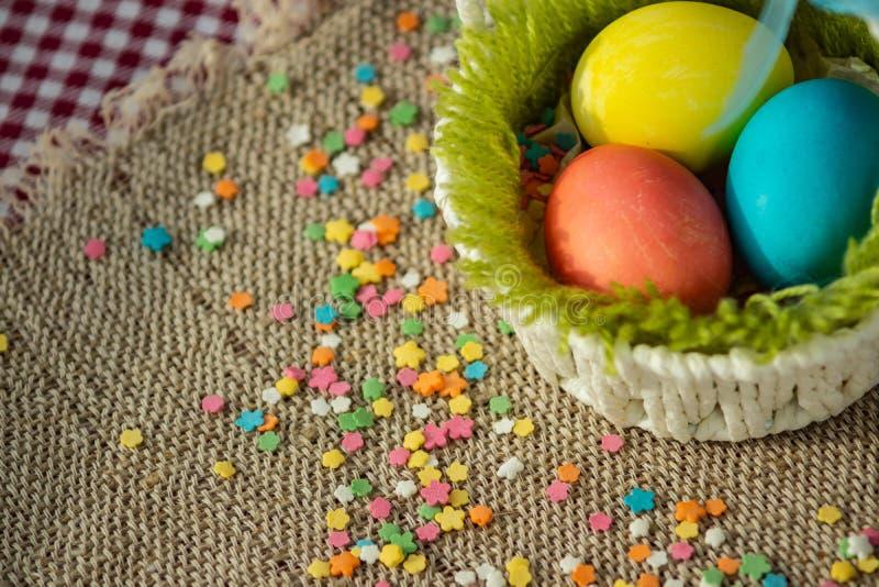 Mångfärgade ägg i easter den festliga korgen på kanfasservett royaltyfria bilder