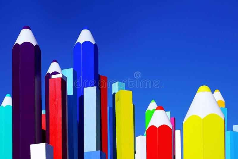 Mångfärgade blyertspennor på en bakgrund av blå himmel arkivbilder