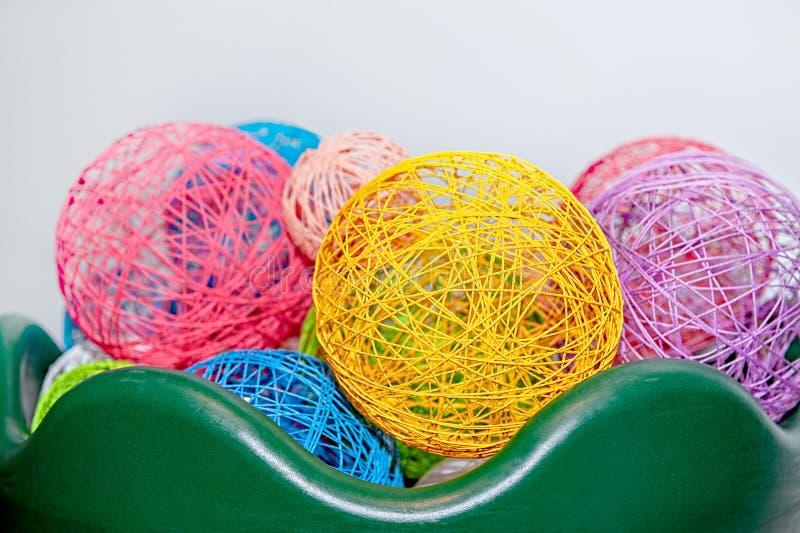 Mångfärgade bollar av trådar i en grön vas precisera sina anklagelser mot white för variation för bakgrundsgarnering inre liten O royaltyfri foto
