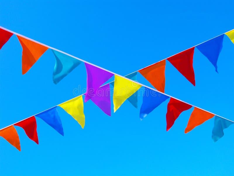 Mångfärgade flaggor som korsar band i himlen royaltyfria foton
