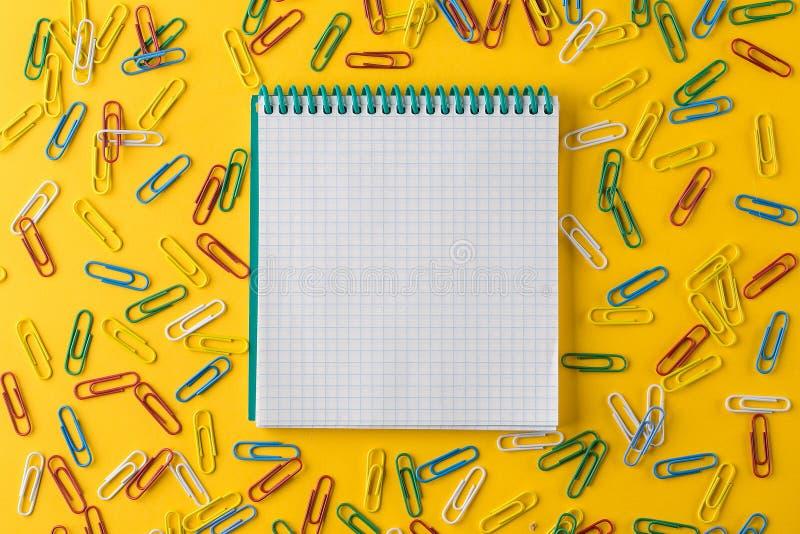 Mångfärgade gemmar och Notepad på en gul bakgrund royaltyfri foto