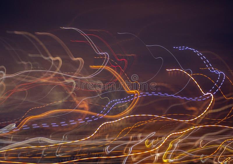 Mångfärgade glödande linjer på en mörk bakgrund arkivbild