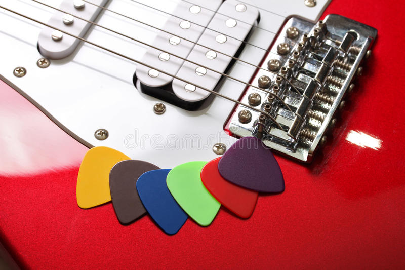 Mångfärgade hackor på en elektrisk gitarr arkivbild