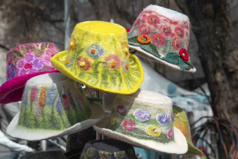 M?ngf?rgade handgjorda kvinnors hattar gjorde av filt med garneringar, och broderi s?ljs i shoppar royaltyfri foto