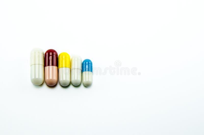 Mångfärgade kapslar med medicin på en vit bakgrund som i storlek fodras royaltyfri bild