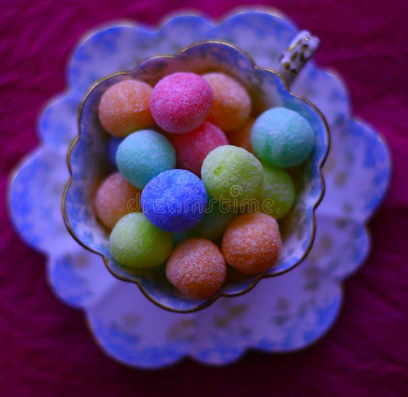 Mångfärgade konfektar i en gammalmodig tekopp arkivfoto