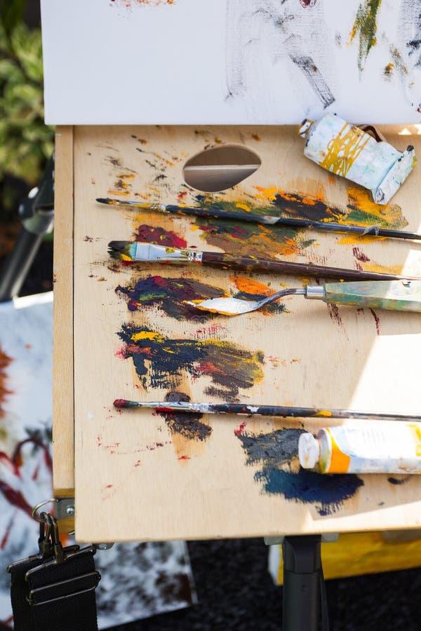 Mångfärgade målarfärger och borstar för att dra, konstnärens arbetsplats stock illustrationer
