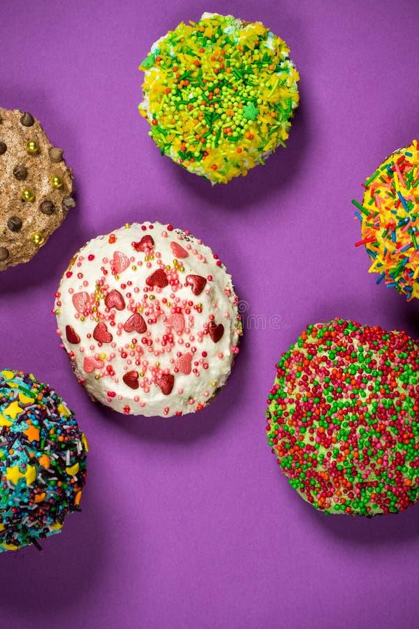 Mångfärgade muffin på lilatabellen royaltyfri fotografi