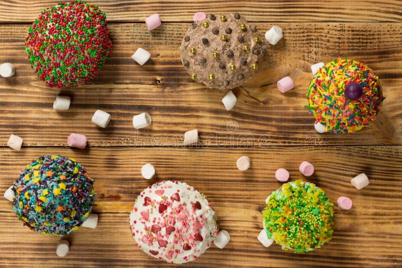 Mångfärgade muffin på trätabellen arkivfoto