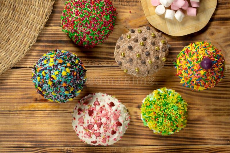 Mångfärgade muffin på trätabellen arkivbilder