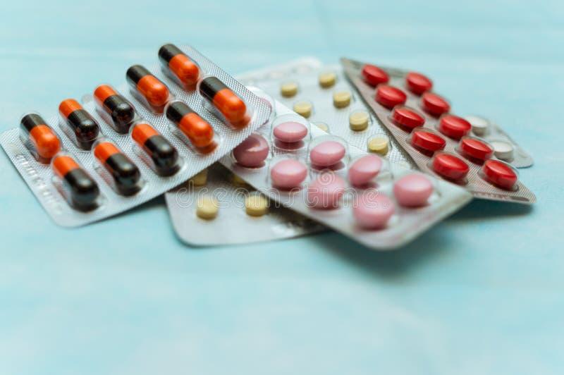 Mångfärgade piller och kapslar i blåsanärbild, på blå bakgrund Begreppet av behandling av mänskliga sjukdomar royaltyfri fotografi