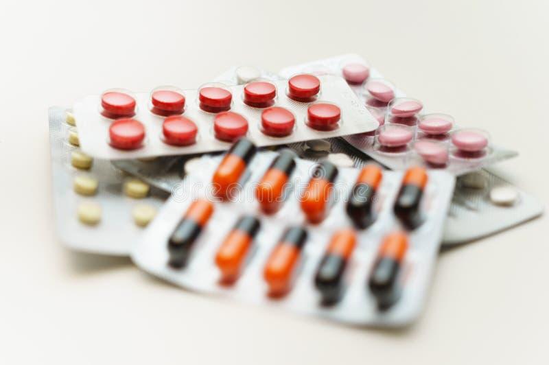 Mångfärgade piller och kapslar i blåsanärbild, på en vit bakgrund slapp fokus Begreppet av behandling av mänskliga sjukdomar arkivbilder