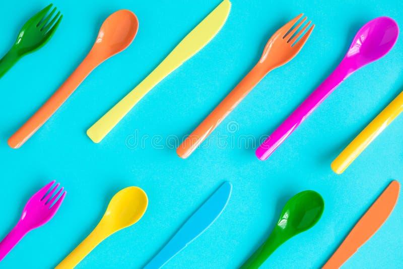 Mångfärgade plast- skedar, gafflar och knivmodell som isoleras på blått arkivbild