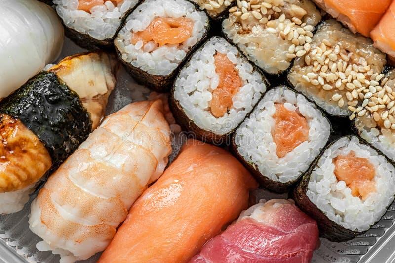 Mångfärgade rullar och sushiris, kaviar och lax, ål, forell på tabellen i bakgrunden royaltyfri fotografi