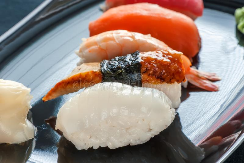 Mångfärgade rullar och sushiris, kaviar och lax, ål, forell på tabellen i bakgrunden fotografering för bildbyråer