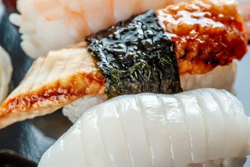 Mångfärgade rullar och sushiris, kaviar och lax, ål, forell på tabellen i bakgrunden royaltyfria foton