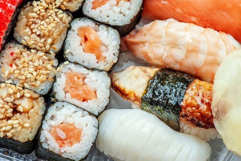 Mångfärgade rullar och sushiris, kaviar och lax, ål, forell på tabellen i bakgrunden royaltyfri bild