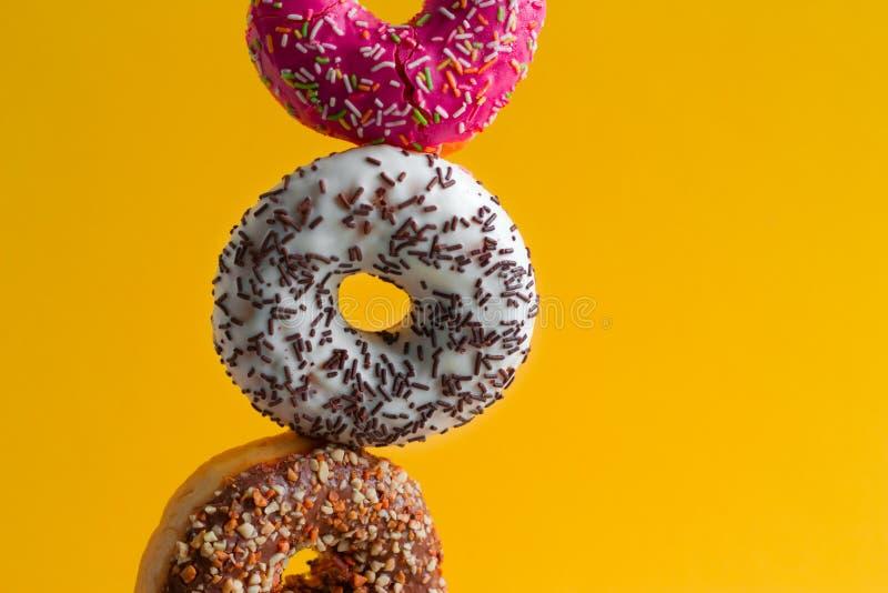 mångfärgade söta donuts med stänk på vibrerande gul bakgrund royaltyfria foton