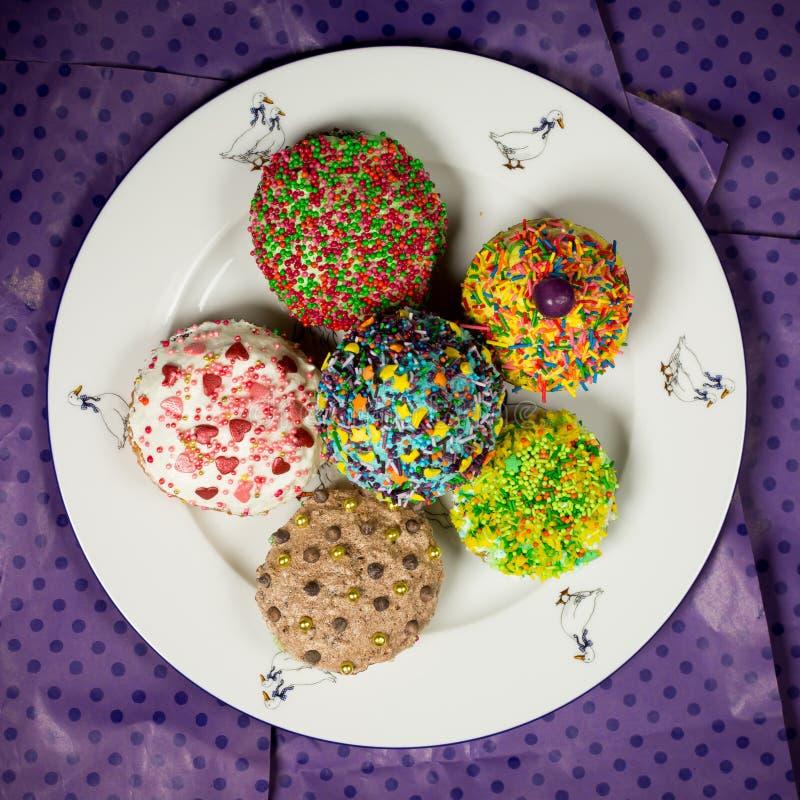 Mångfärgade söta muffin på den vita plattan, purpurfärgad bakgrund, matfoto fotografering för bildbyråer